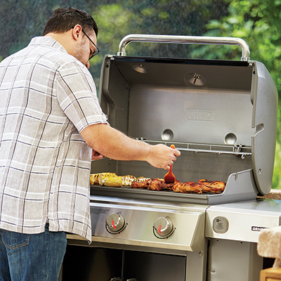 A man bastes chicken on the grill