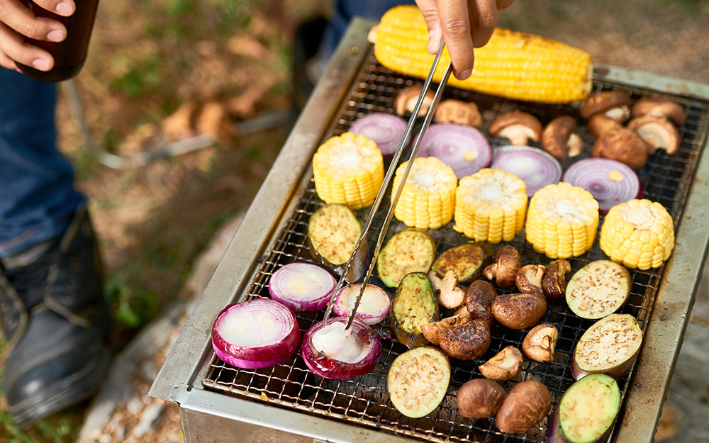 Sliced corn, eggplant and other vegetables cook on a grill.