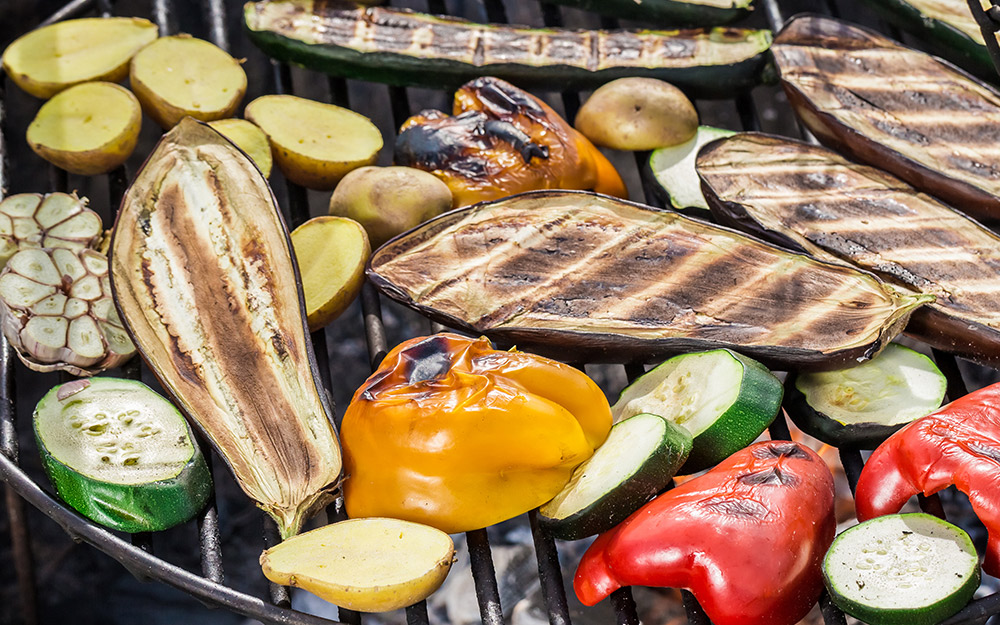 Eggplant, peppers and other vegetables cook on a grill.