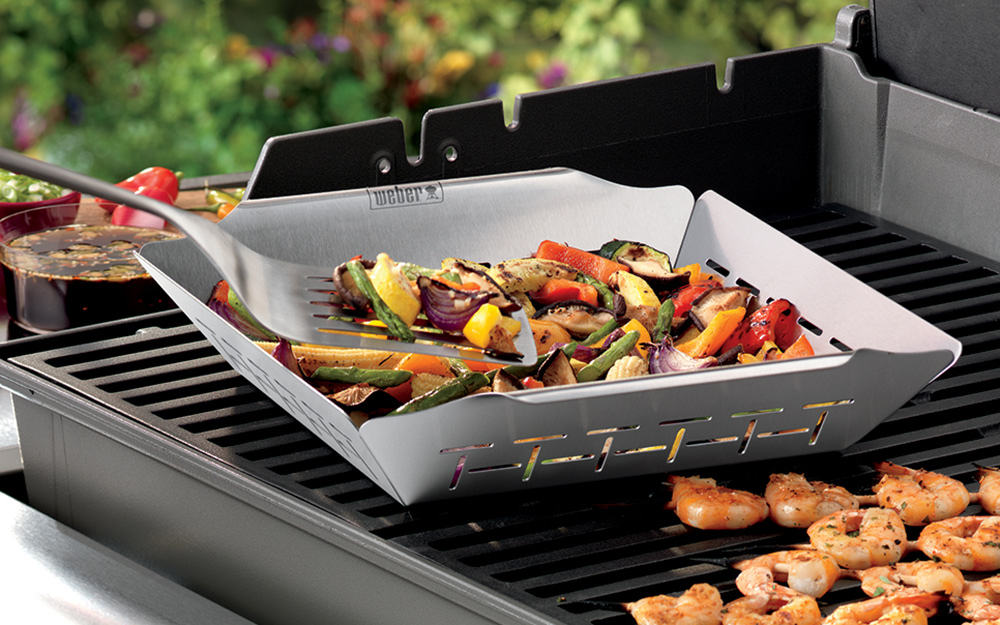 Vegetables cook in a grill basket.