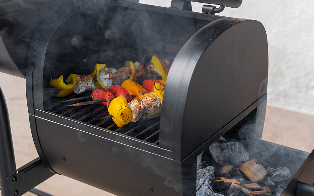 Vegetable skewers cook in a smoker.