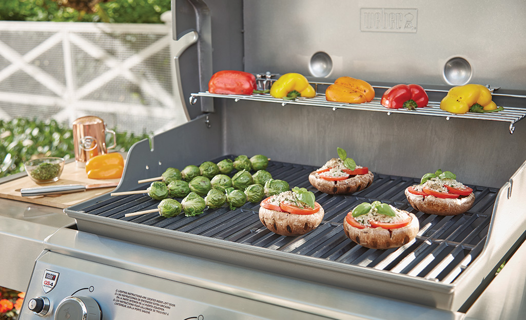 Brussels sprouts, peppers and other vegetables cooking on a gas grill.