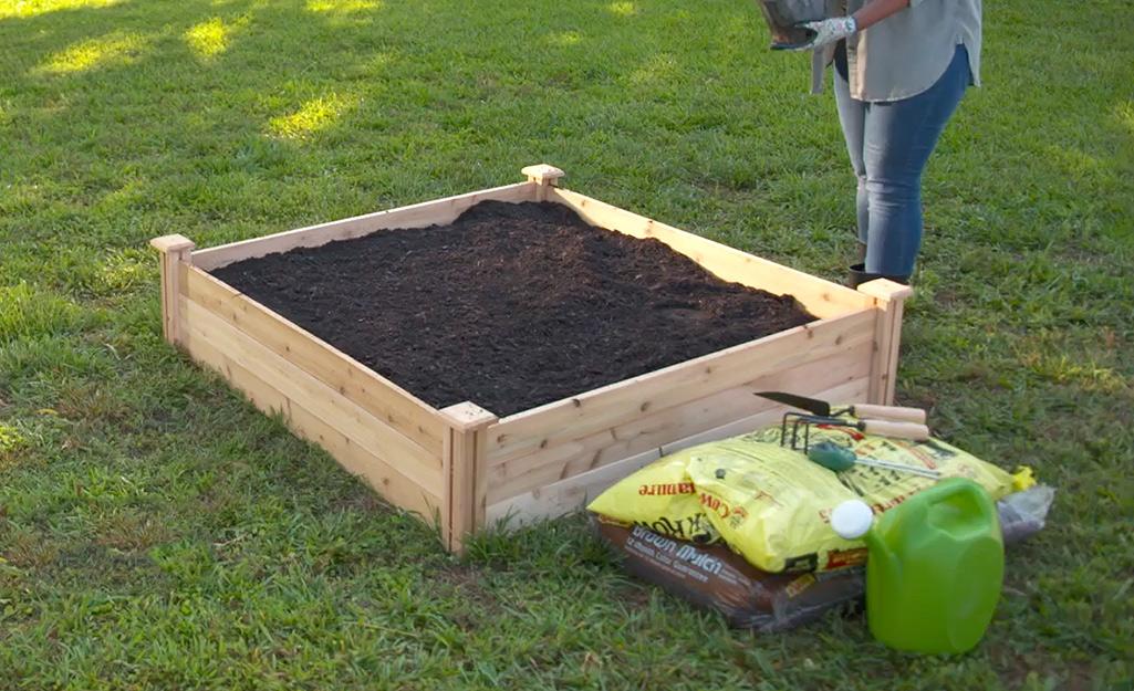 A gardener gathers supplies.