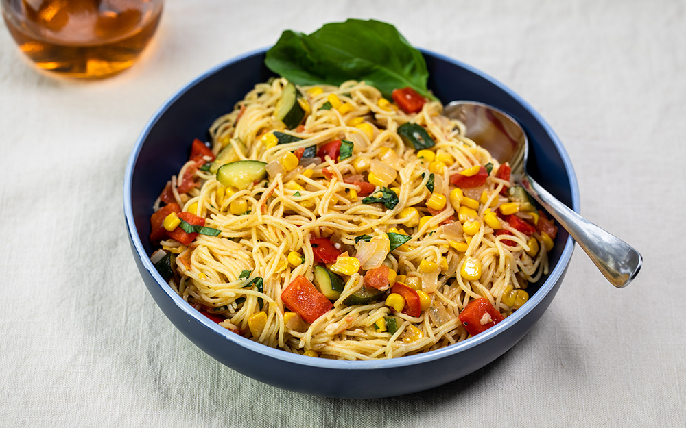 Bowl of pasta with summer vegetables and basil