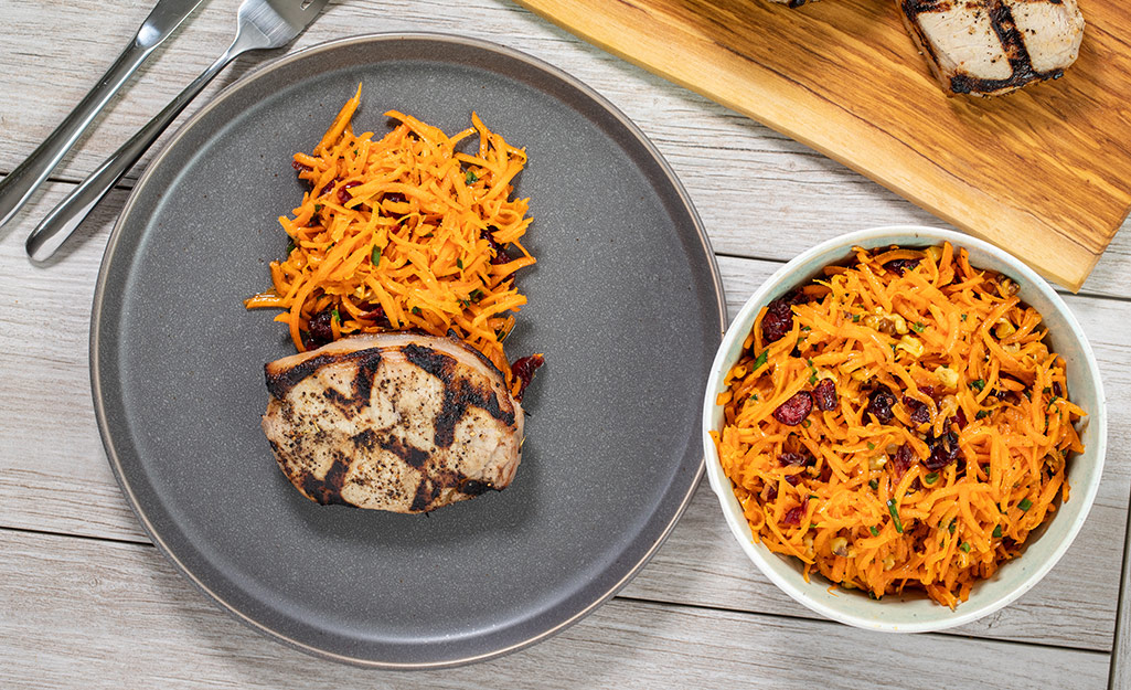 Carrot cranberry slaw with pork chop on a plate