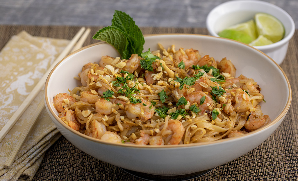 Shrimp pad Thai with cilantro in a white bowl with limes