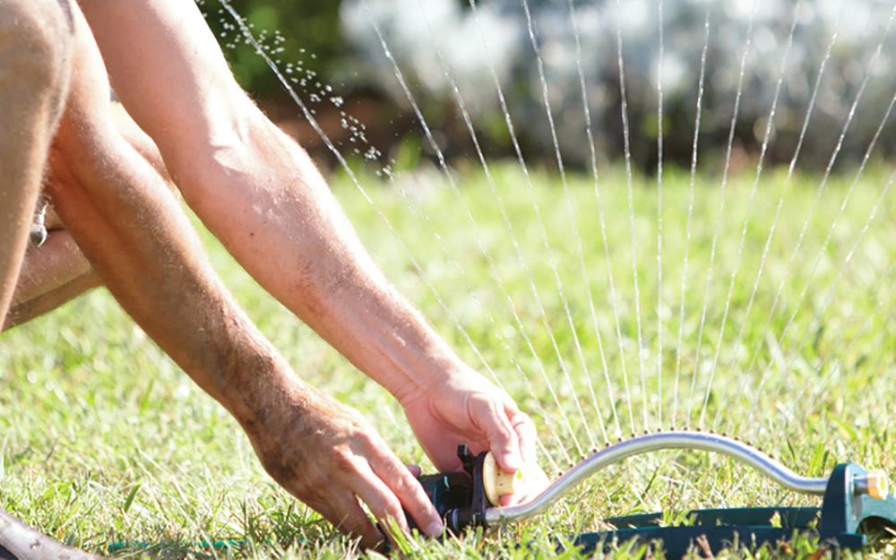 person turning on sprinkler system to water lawn