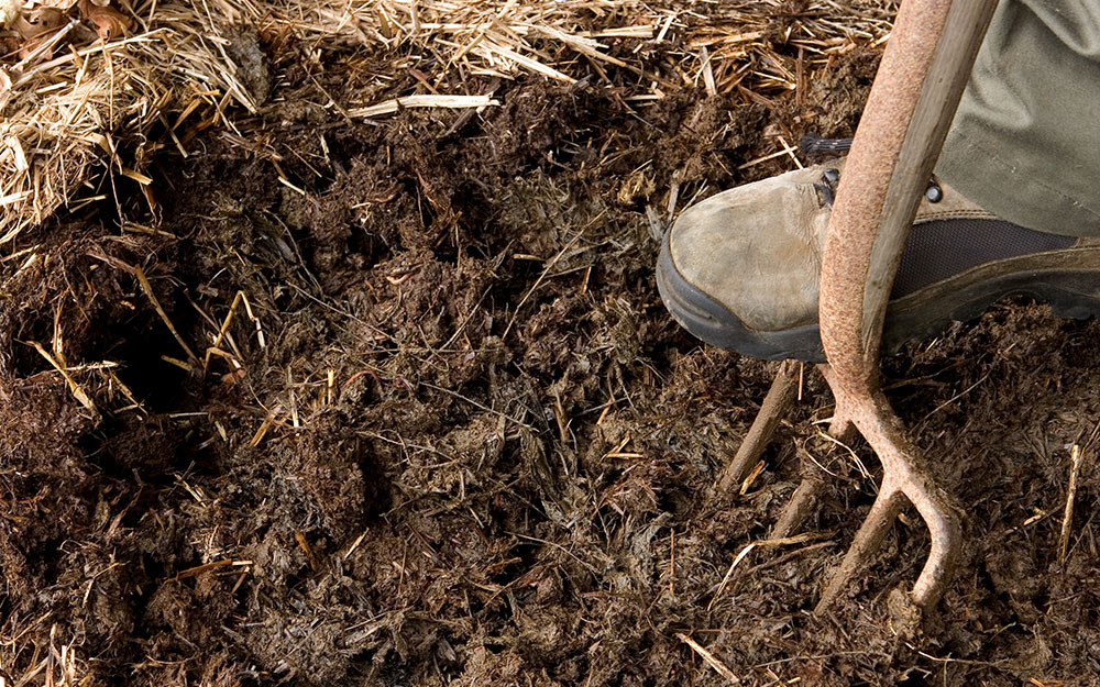 A person digging into soil with a garden fork.