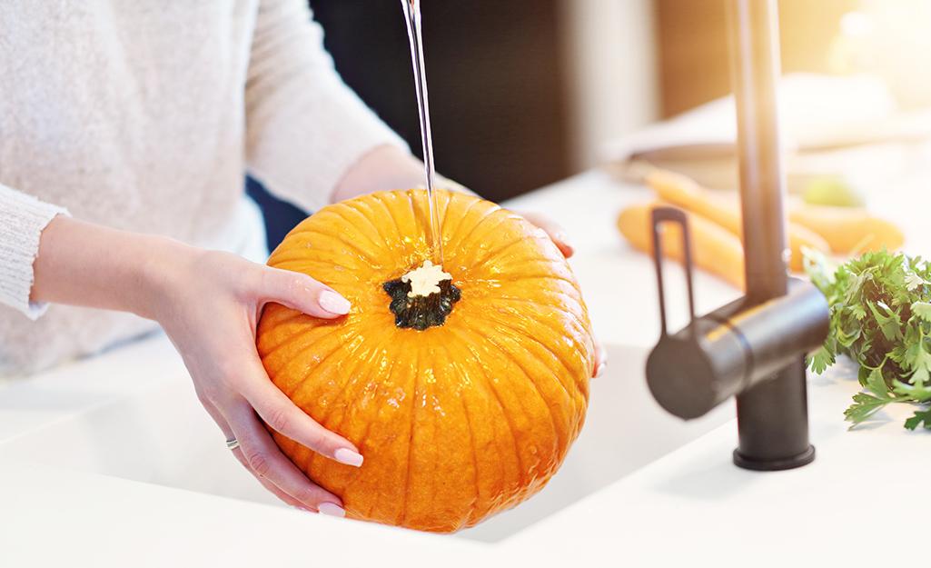 Rinsing a pumpkin in a sink
