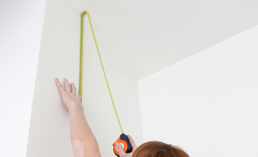 Someone measuring from the ceiling with a tape measure.