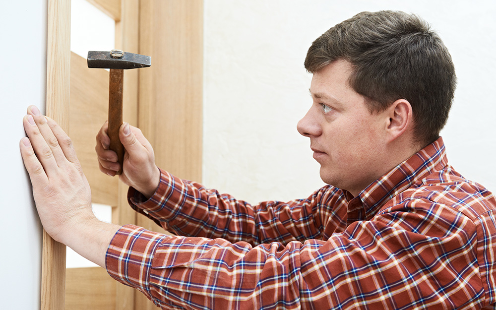man using a hammer to put nails in a doorframe