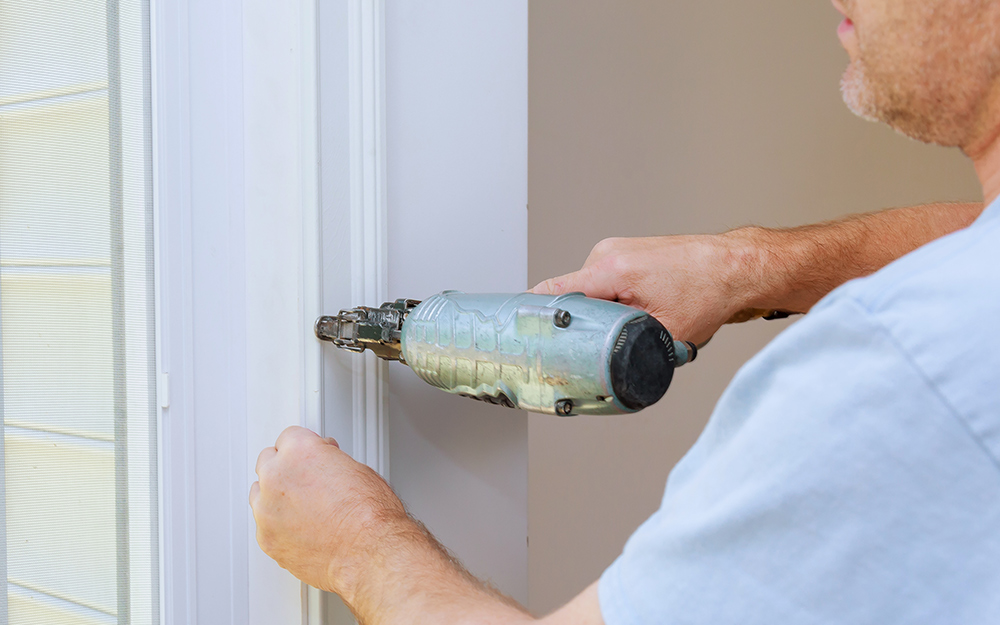 man attaching hardware to door using a drill