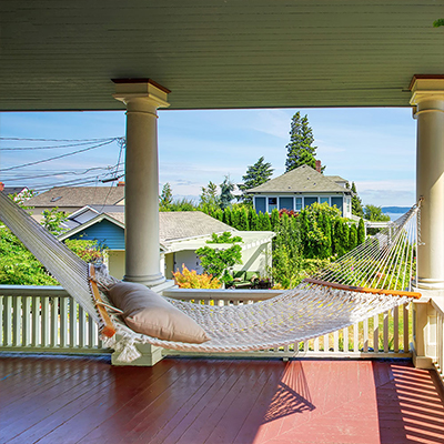 A rope hammock on a porch overlooking houses near an ocean.