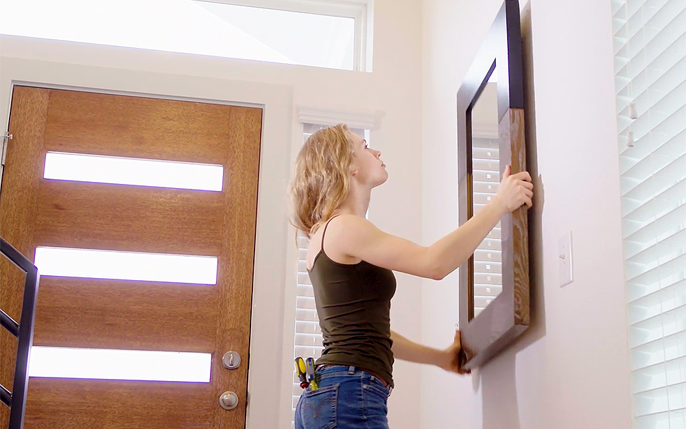 A person hangs a large framed mirror on the wall of an entry hallway.