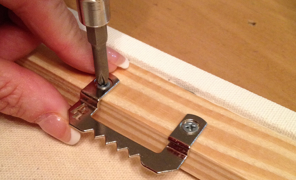 A hand installing screws into a frame.
