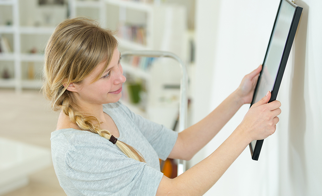 A woman hanging a picture frame on a wall.
