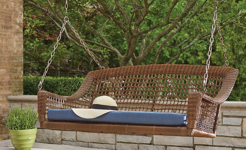 A wicker porch swing with a blue cushion.