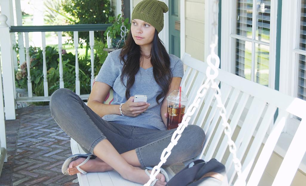 A woman sitting on a white porch swing.