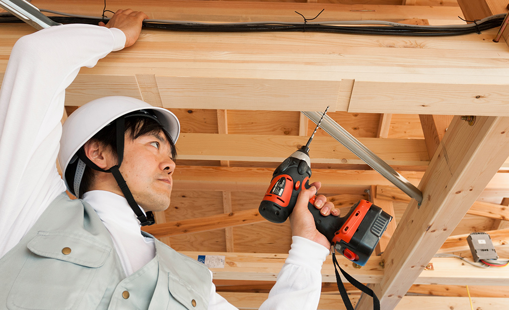 A person drilling a hole into a joist.