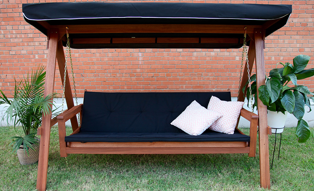 A freestanding wood swing with black cushion.