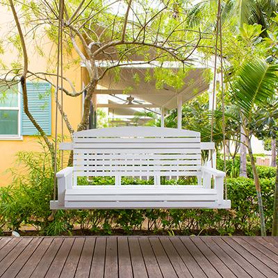 A white porch swing on a porch.