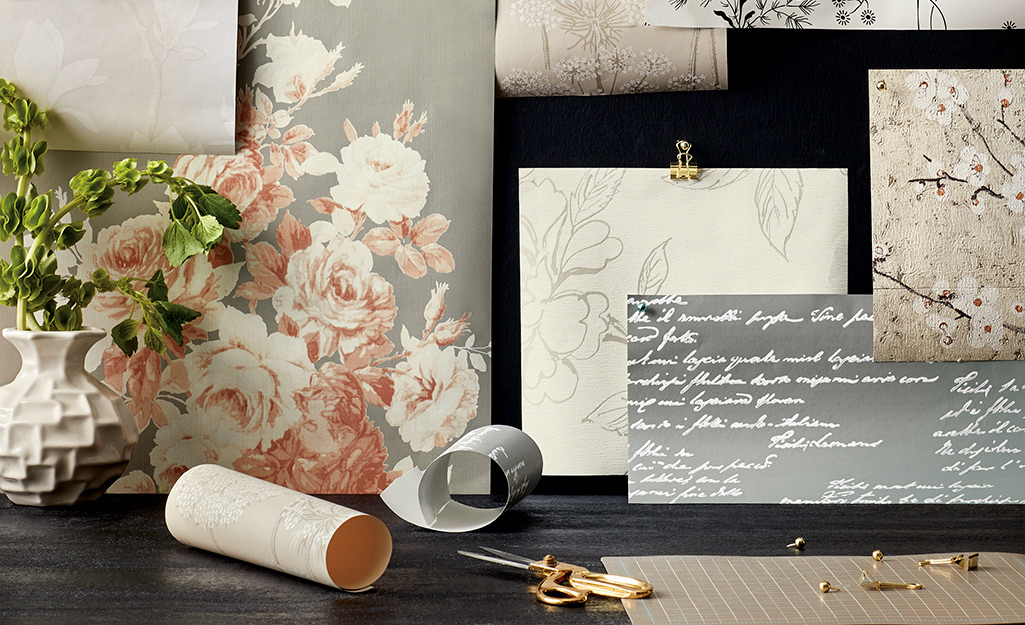 Snippets of wallpaper borders artistically arranged near a plant in a vase.