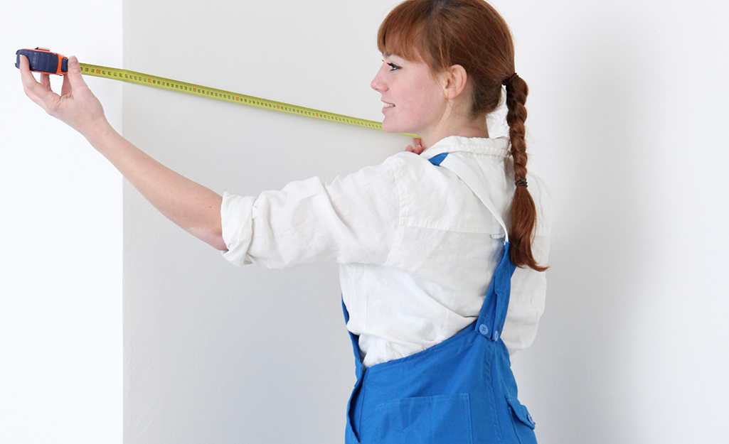 A woman measuring a wall with a measuring tape.