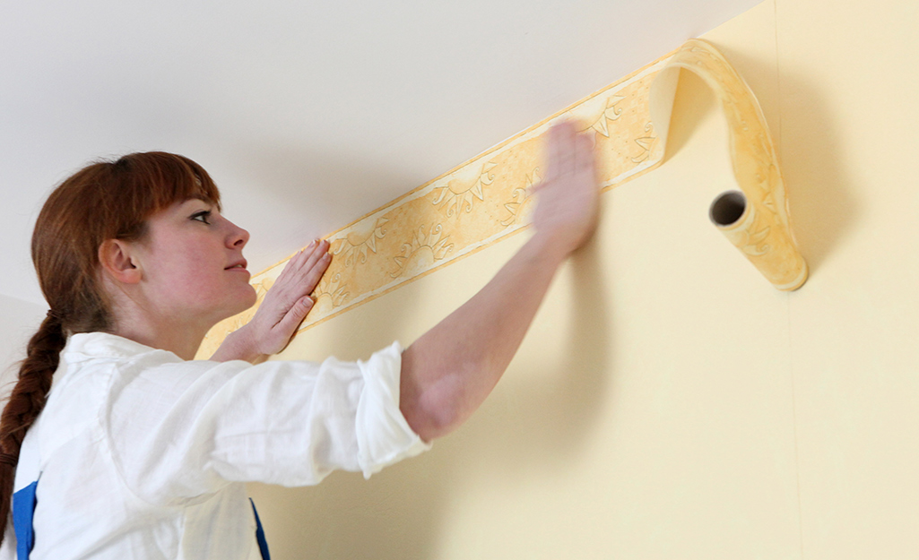 A woman laying a wallpaper border along a ceiling.