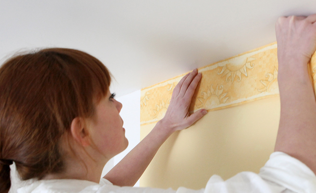 A woman aligns the pattern on a wallpaper border along a ceiling.