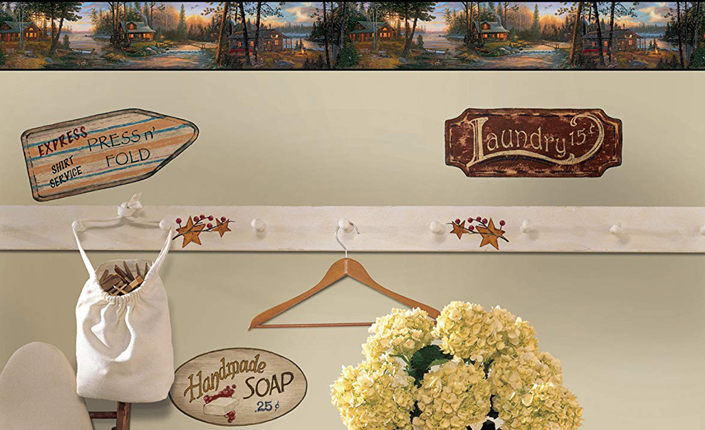 A wallpaper border hangs above a chair rail with hooks in a laundry room.