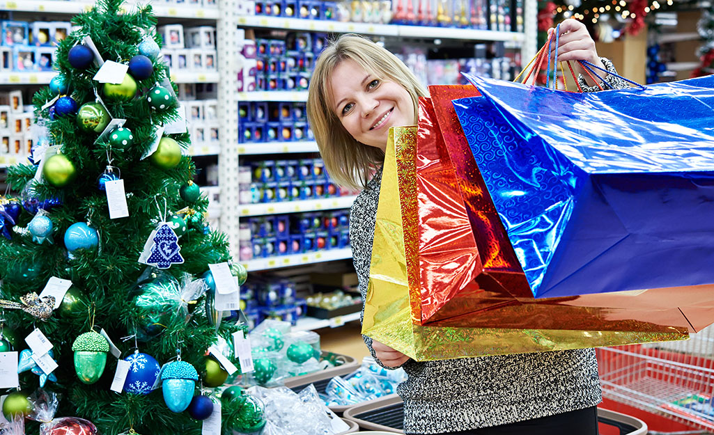 A woman carrying color bags standing next to a Christmas tree.