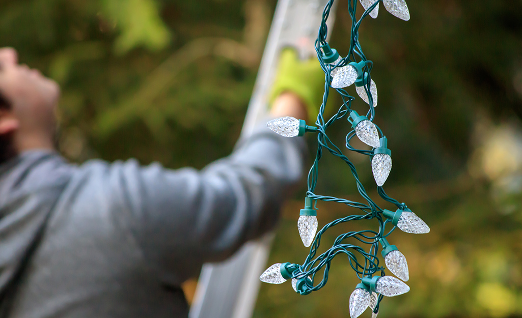 A person hanging up Christmas lights.