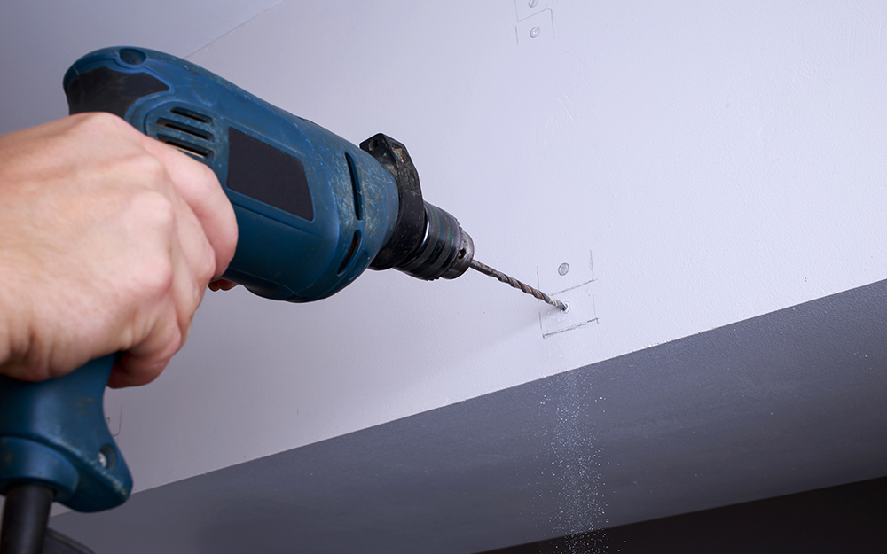 A person drilling a hole on the wall for curtain rod installation