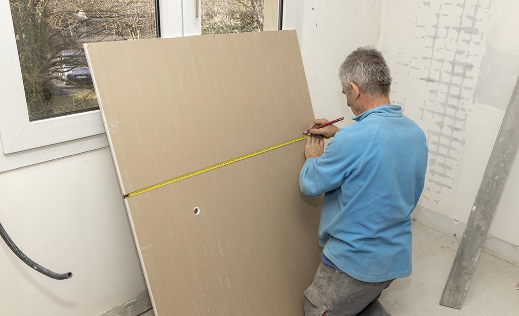 Человек замеряет и маркирует гипсокартон.
