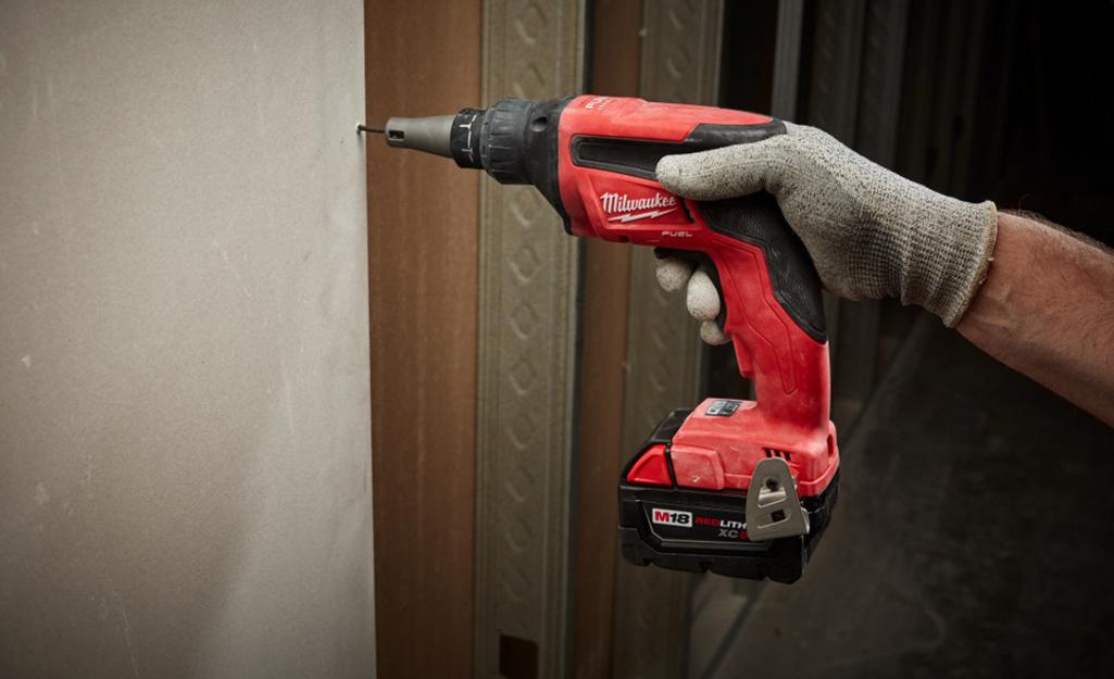 Человек, использующий дрель для ввинчивания гипсокартона в стену.