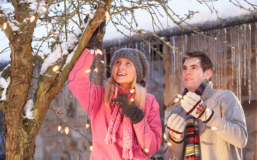 two people hanging outdoor string lights