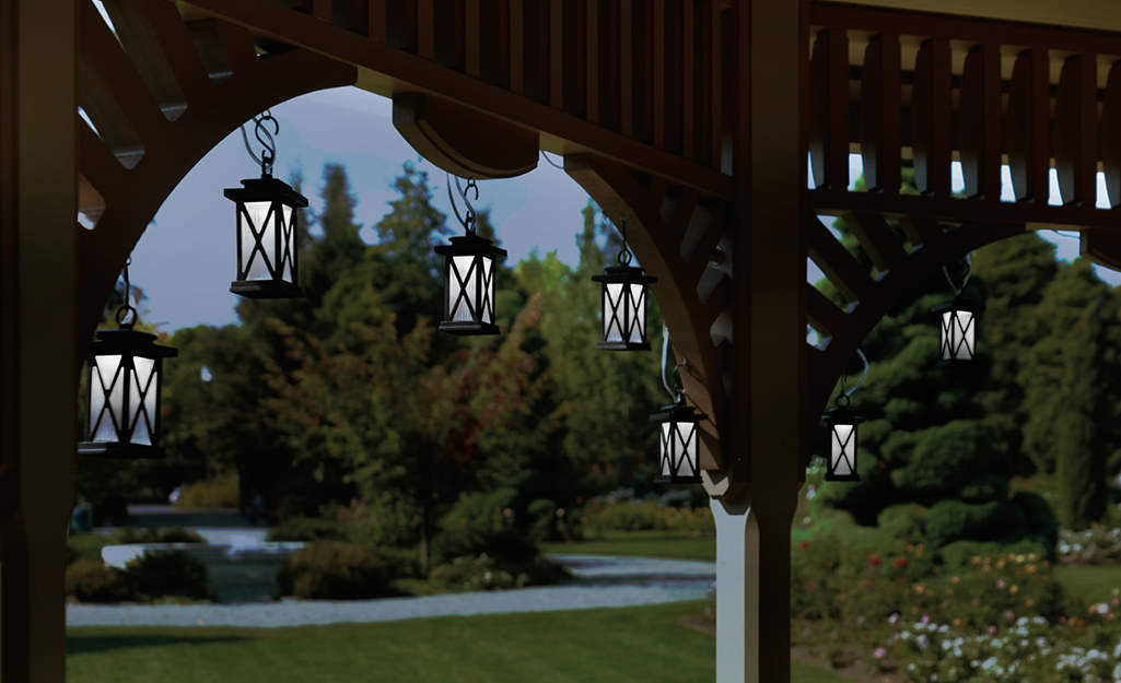 Lantern-shaped string lights hanging from an arbor.