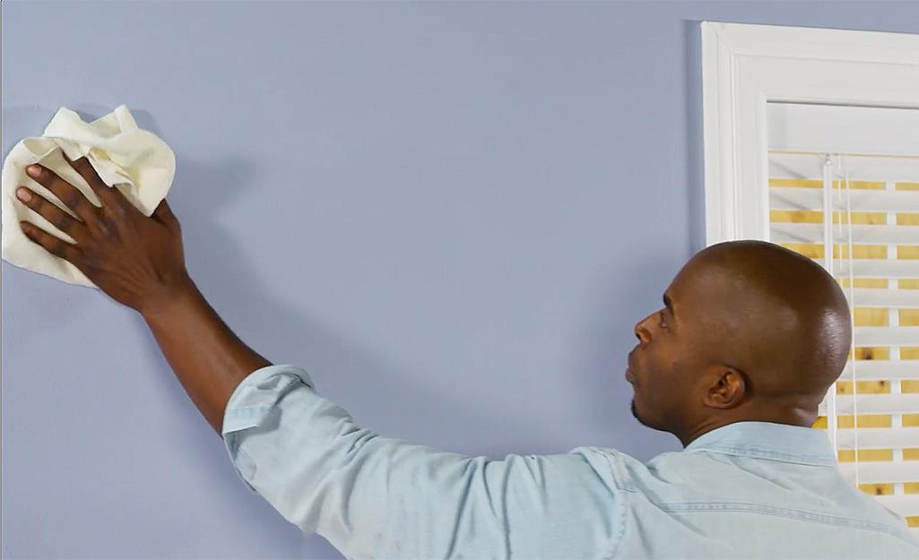 Người đàn ông đang lau bề mặt tường.