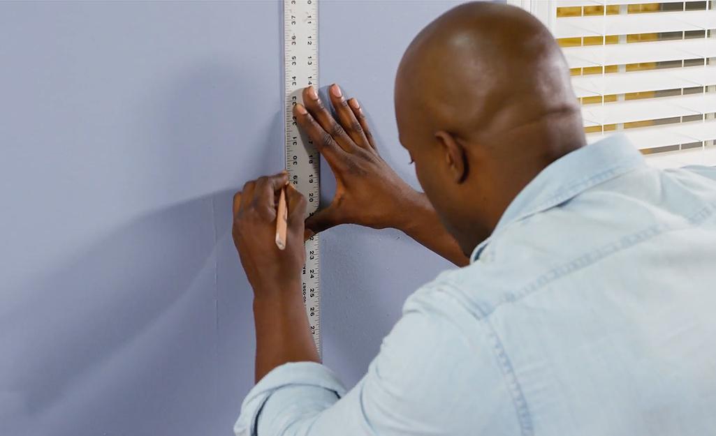 Người đàn ông đang đo một bức tường.