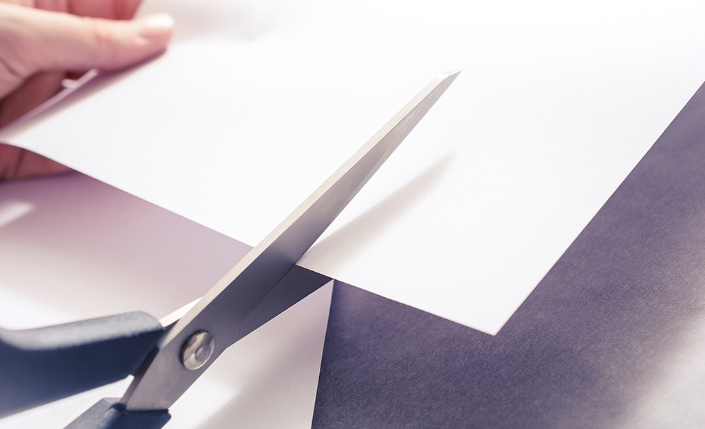 Someone using scissors to cut plate templates out of a sheet of paper.