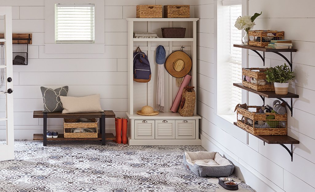 A mudroom with shelves installed on decorative shelving brackets on the wall.