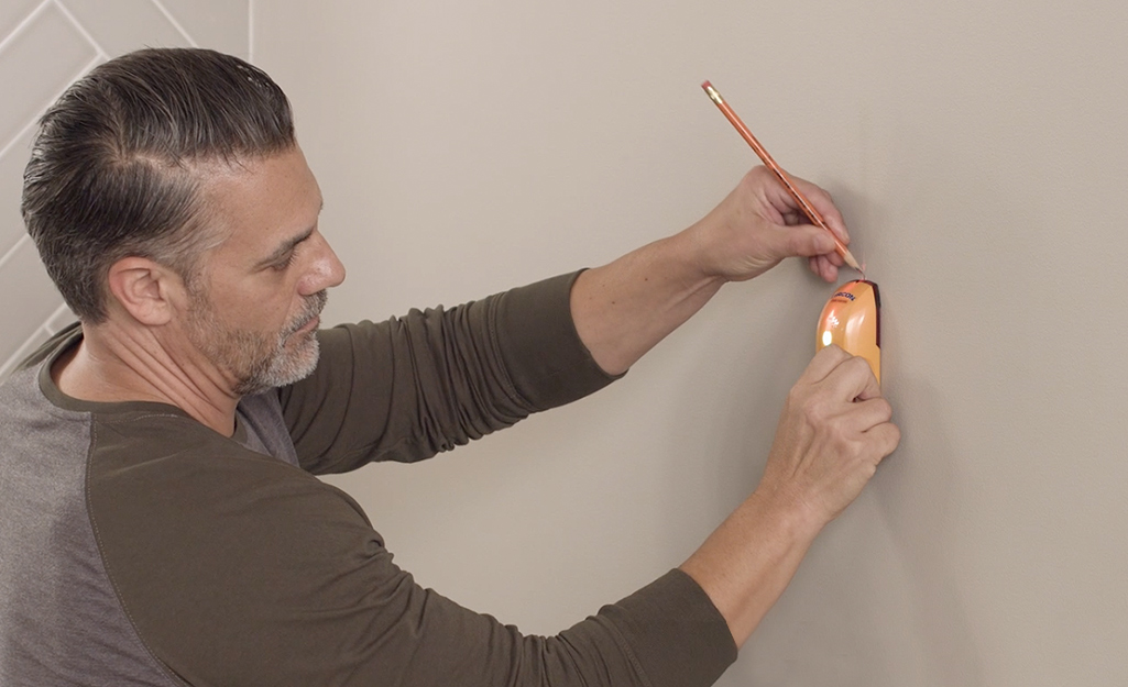 A man using a stud finder to mark the location of a wall stud.