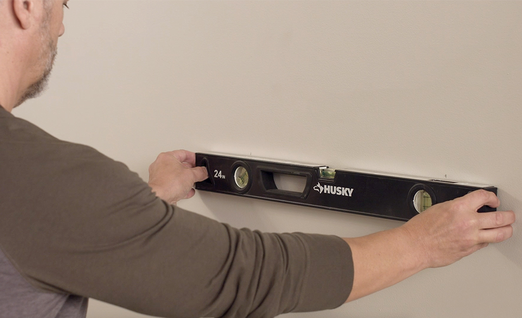 A man using a carpenter's level to check the level of planned shelf bracket locations.