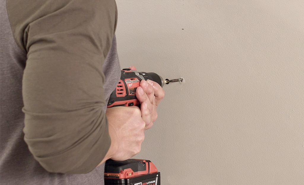 A man drilling pilot holes into drywall.