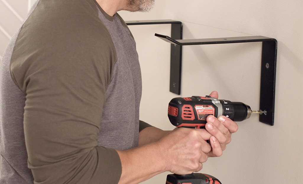 A man securing shelving brackets to drywall using screws and a power drill.