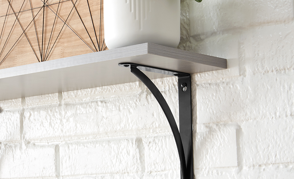 Shelving brackets installed on a painted brick wall.