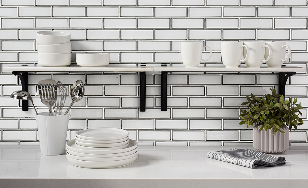 Shelving brackets installed on a kitchen tile wall.