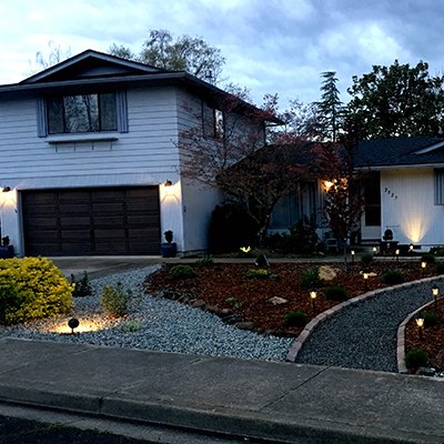 A home is well-lit with outdoor landscape lighting.