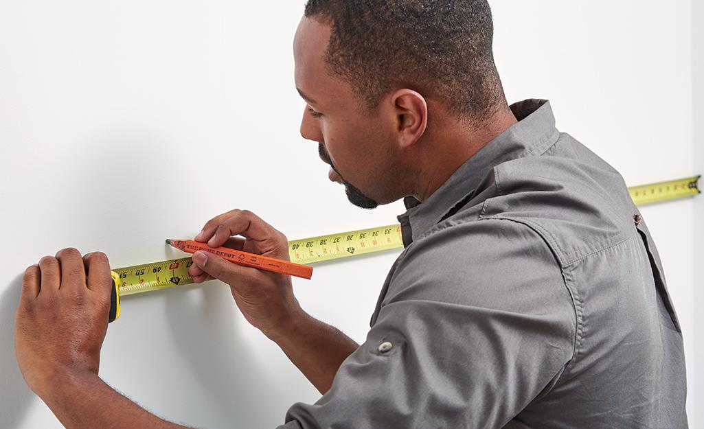 Man measuring wall horizontally for FRP paneling.