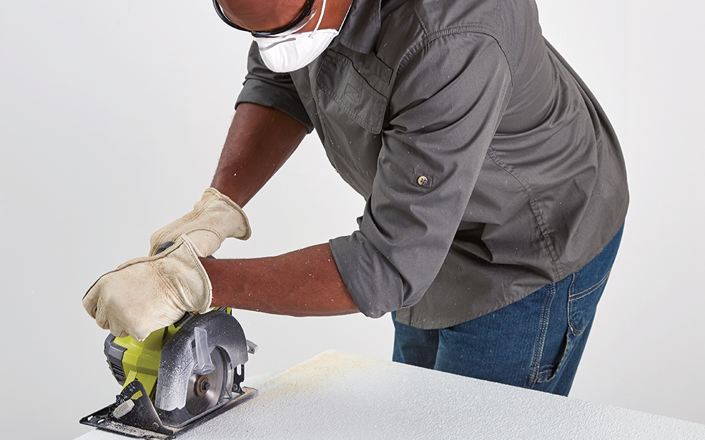 Man cutting FRP paneling with table saw and wearing mask.